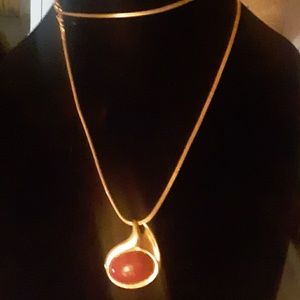 Long gold toned chain with red/gold pendant